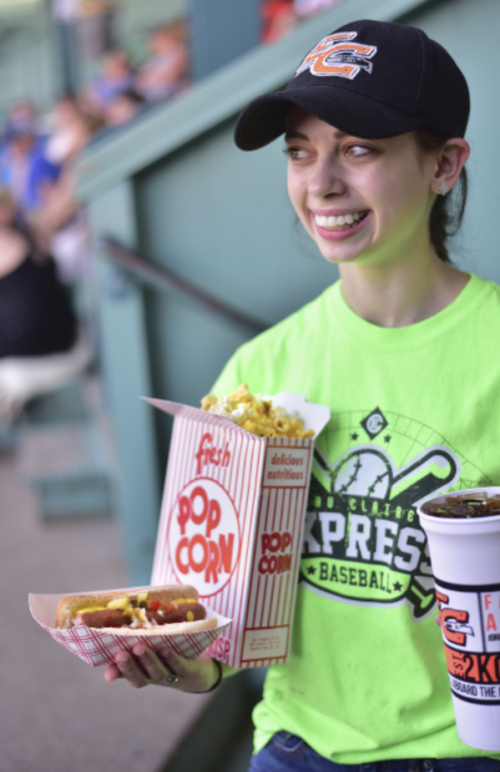 Girl at an Eau Claire Express game with popcorn, hotdog and coke