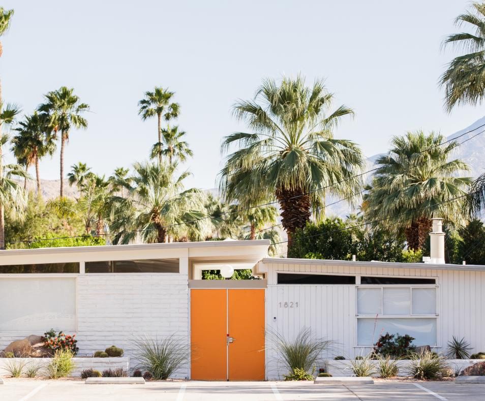 The Amado front entrance welcomes guests with bright orange doors
