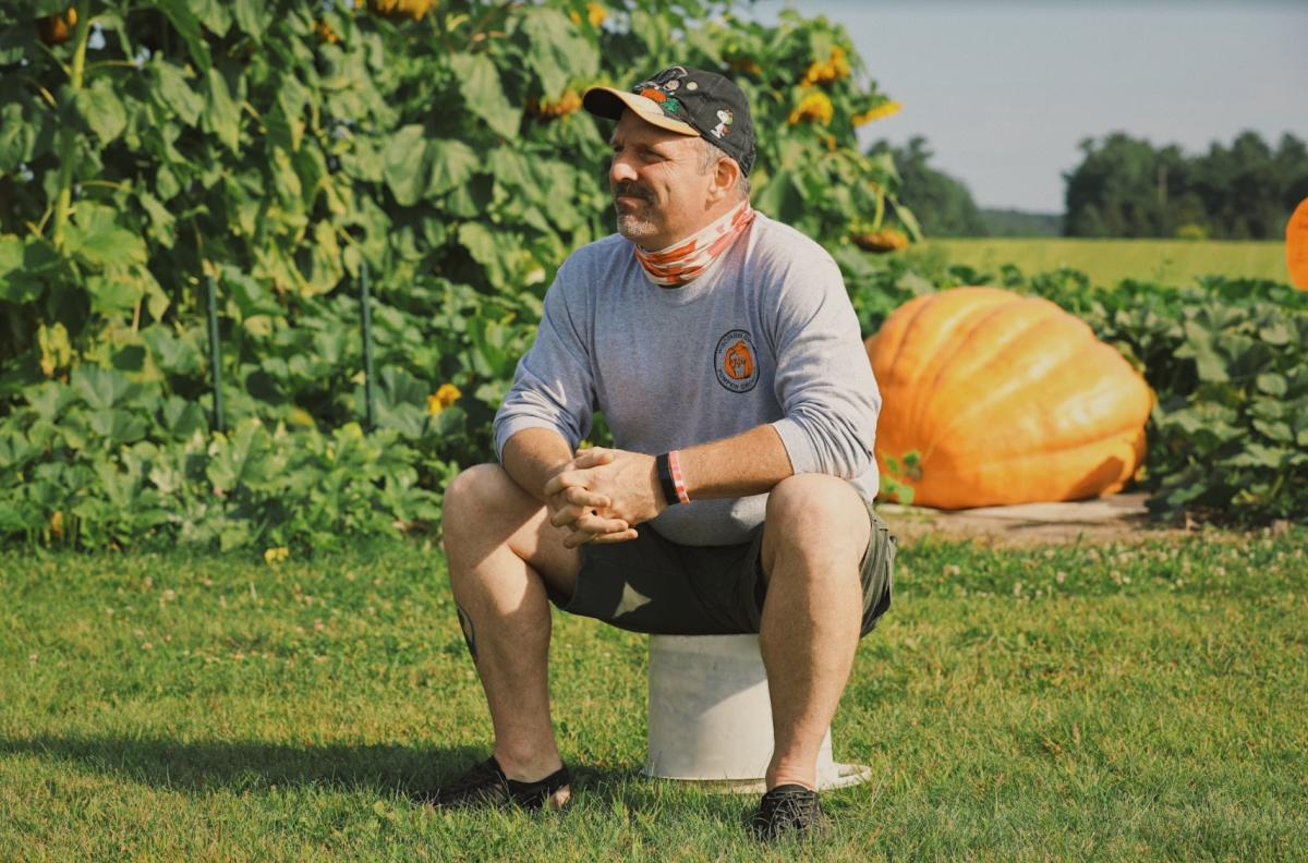 Shannon Engel, giant pumpkin grower, sitting in front of his pumpkin patch
