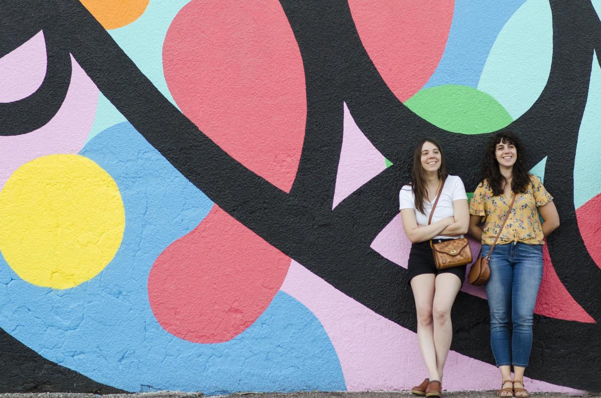 2 people posing in front of one of the murals located in downtown Eau Claire