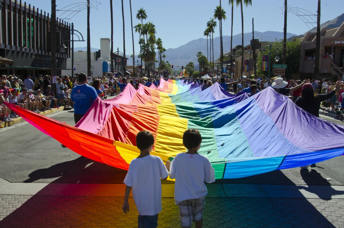 Two children holding pride flag.