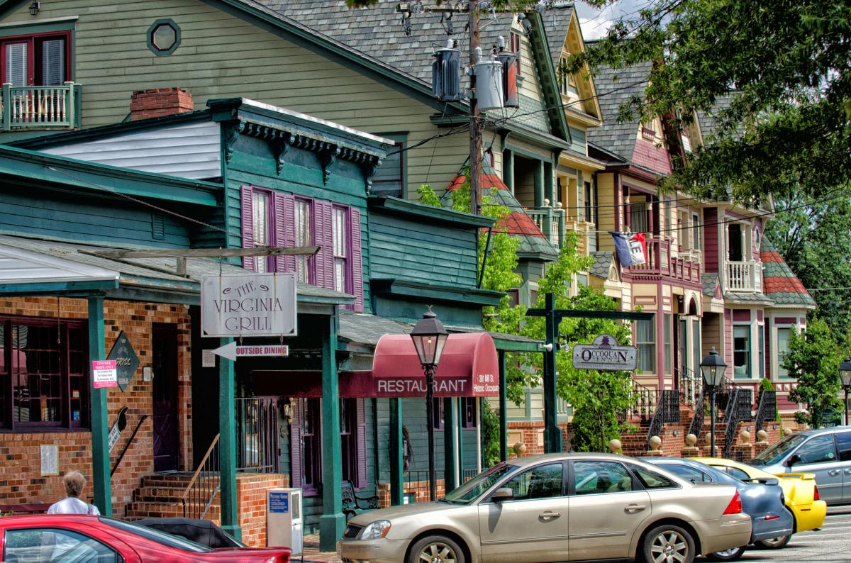 Colorful historic storefronts with cars parked outfront