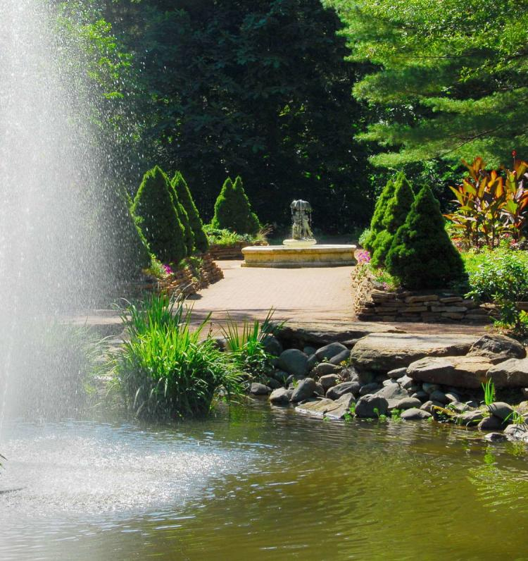 A large fountain sprays water over a flower bed. A path behind the flowers leads up to a sculpture.