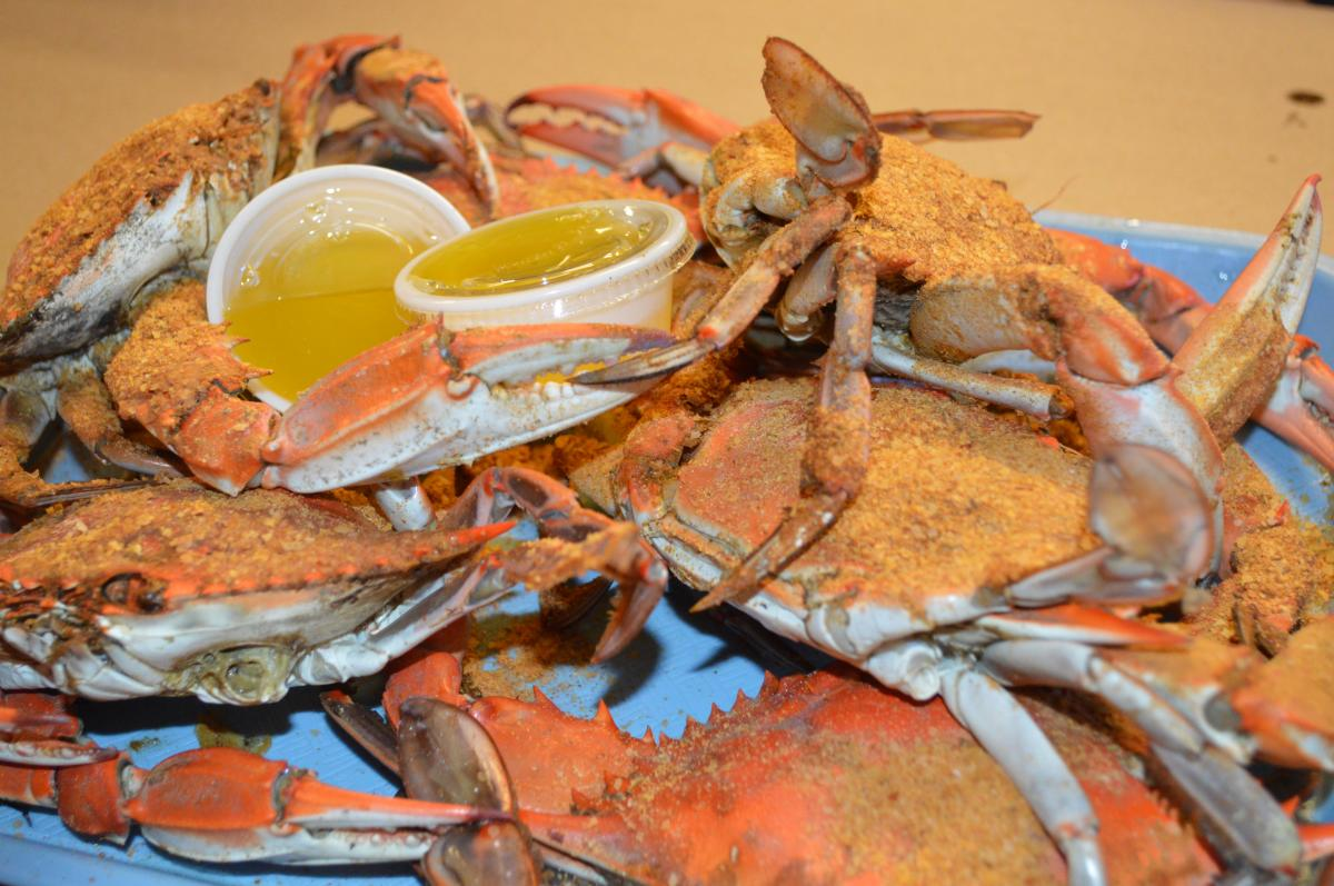 whole crabs with tubs of butter on a platter