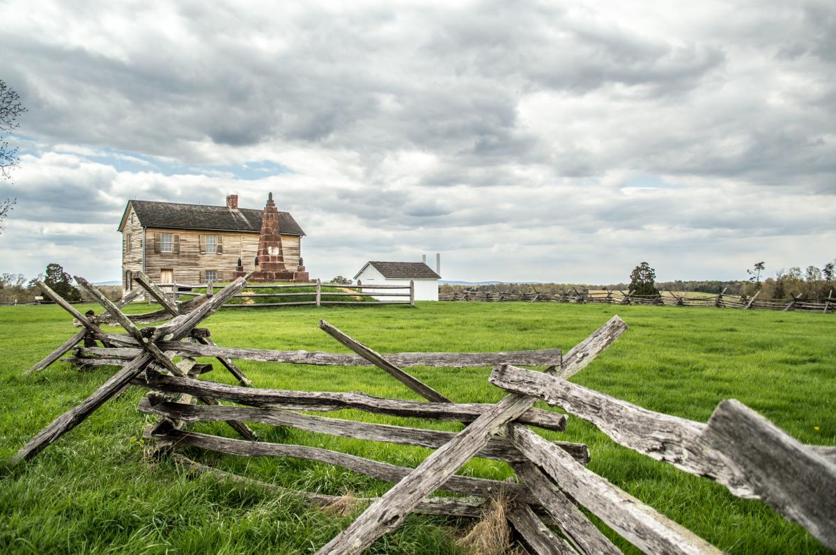 A battlefield with a wooden fence and a historic building in the background