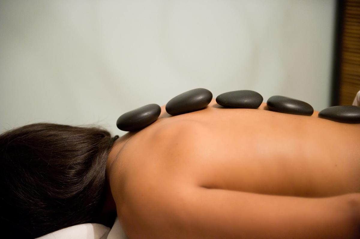 Woman with hot stones along spine at the River Spa in Lafayette