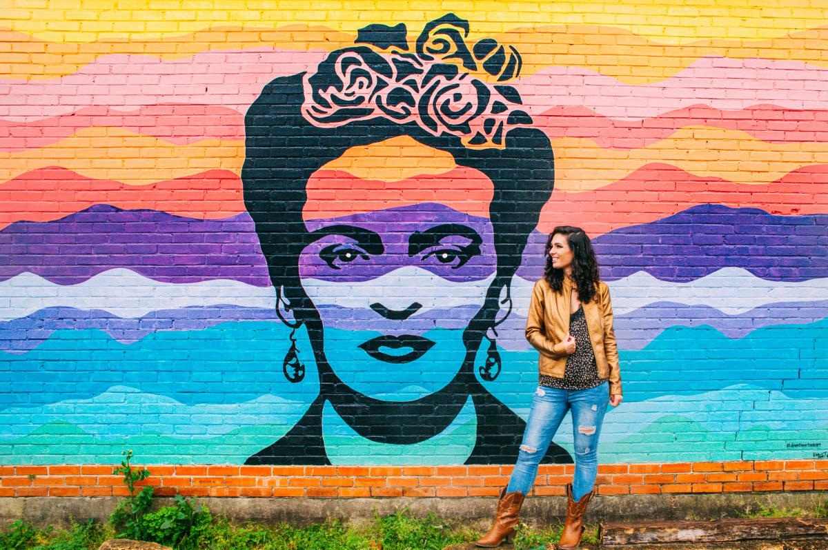 A visitor poses next to the Frida Mural on the Beaumont Mural Walk.