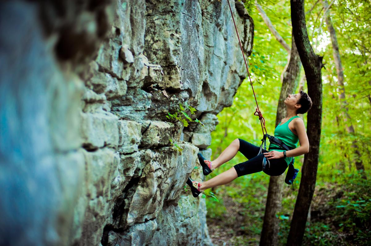 A woman rock climbing on Stone Cuts Trail at Monte Sano Mountain, AL