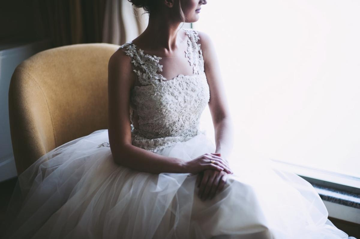 woman in white wedding dress sitting near window