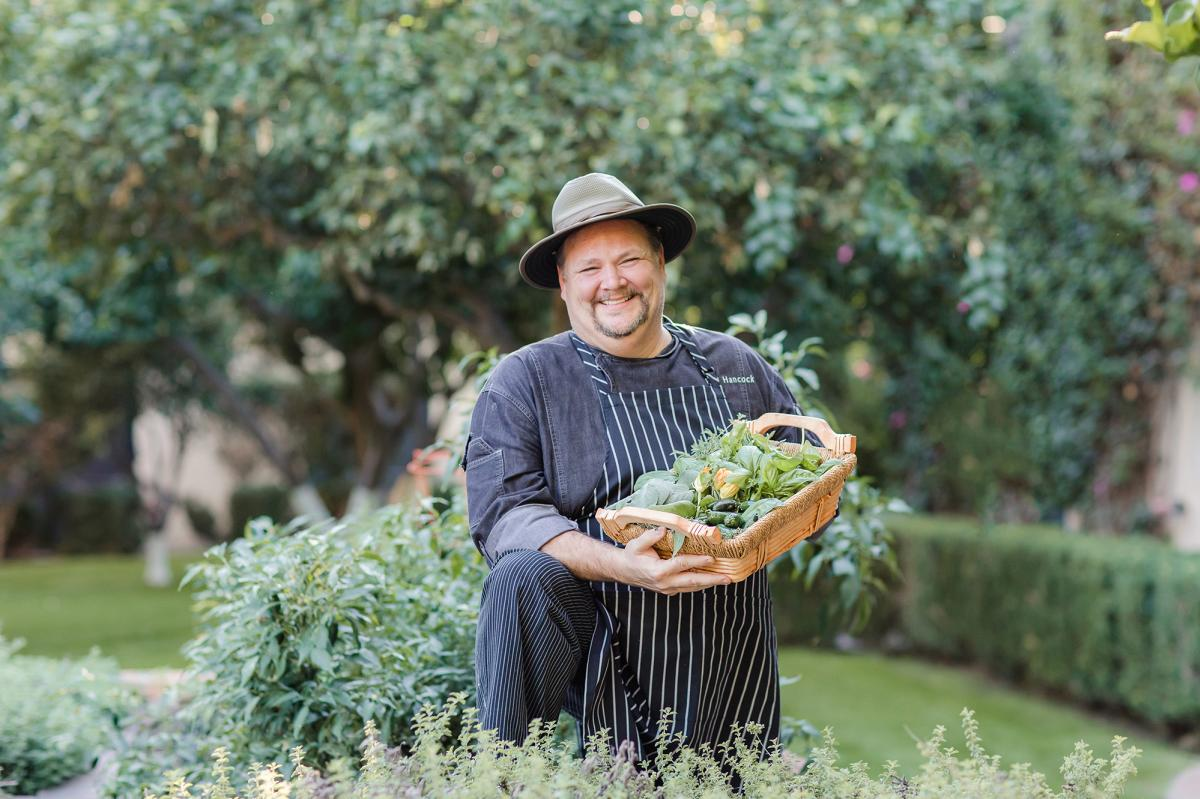 Smiling chef in garden holding a basket