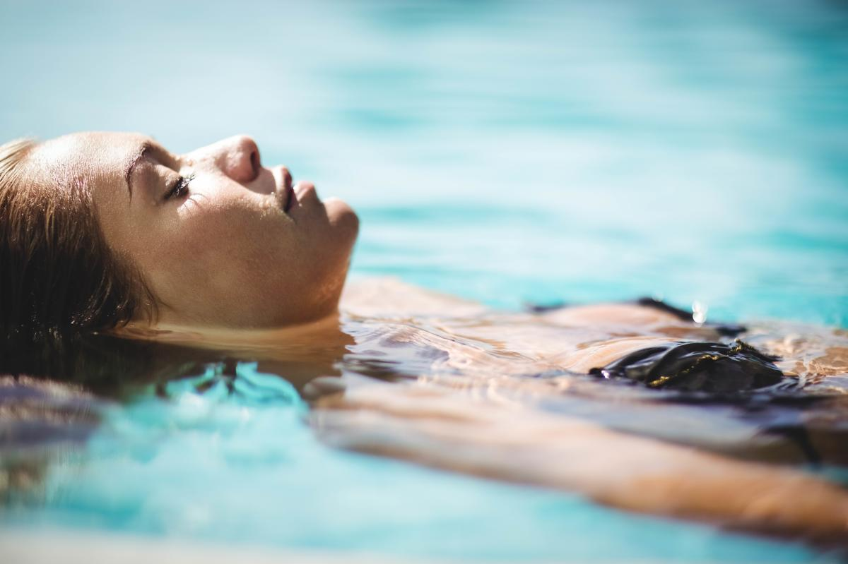 Woman floating in water with eyes closed