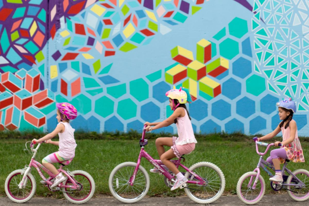 Girls biking by mural