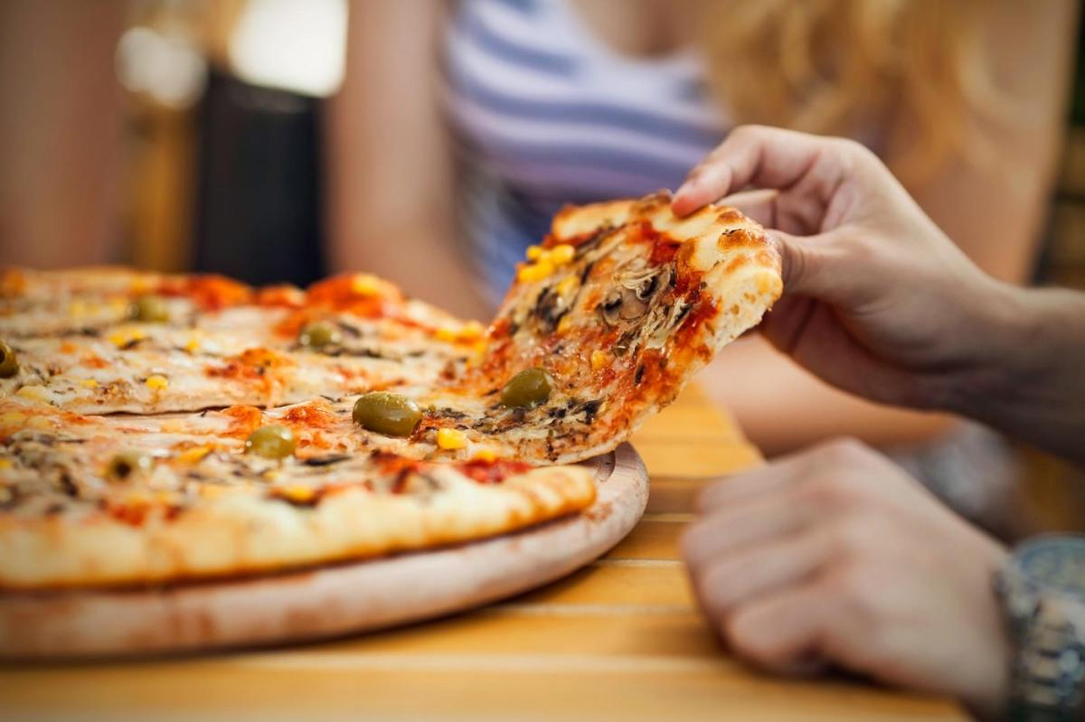 Person Pulling a Slice of Pizza