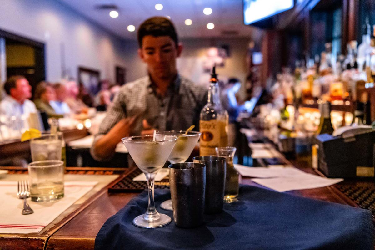 A bartender preparing drinks for seated patrons at Halyards Restaurant on St. Simons Island, GA