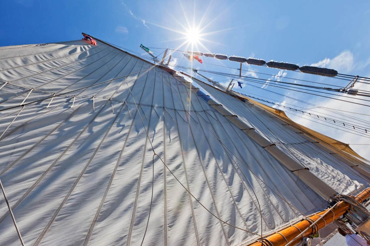 View of the mast and sails on a BaySail Appledore Tall Ship with the sun overhead