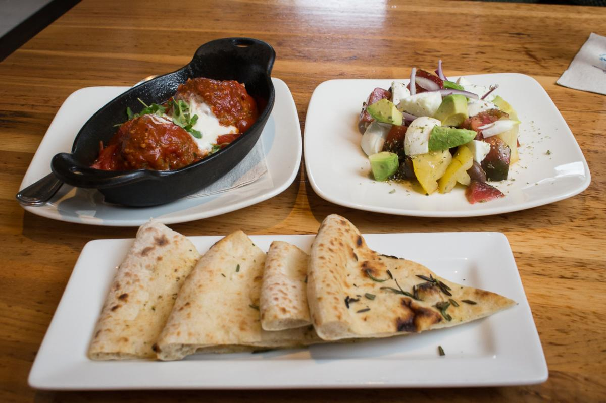 3 dishes of meatballs, flat bread, and pomodori