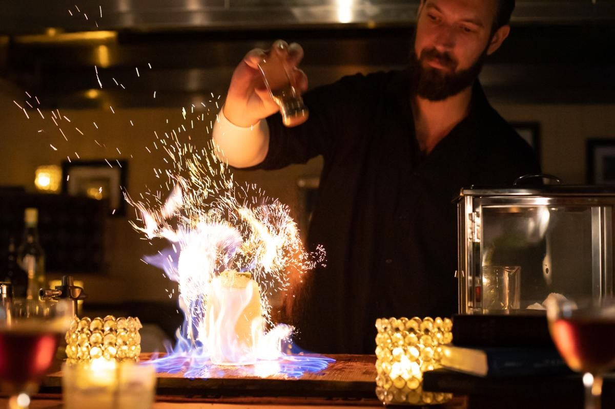 A bartender at The Butchershop sets the Tiki God Cocktail on fire