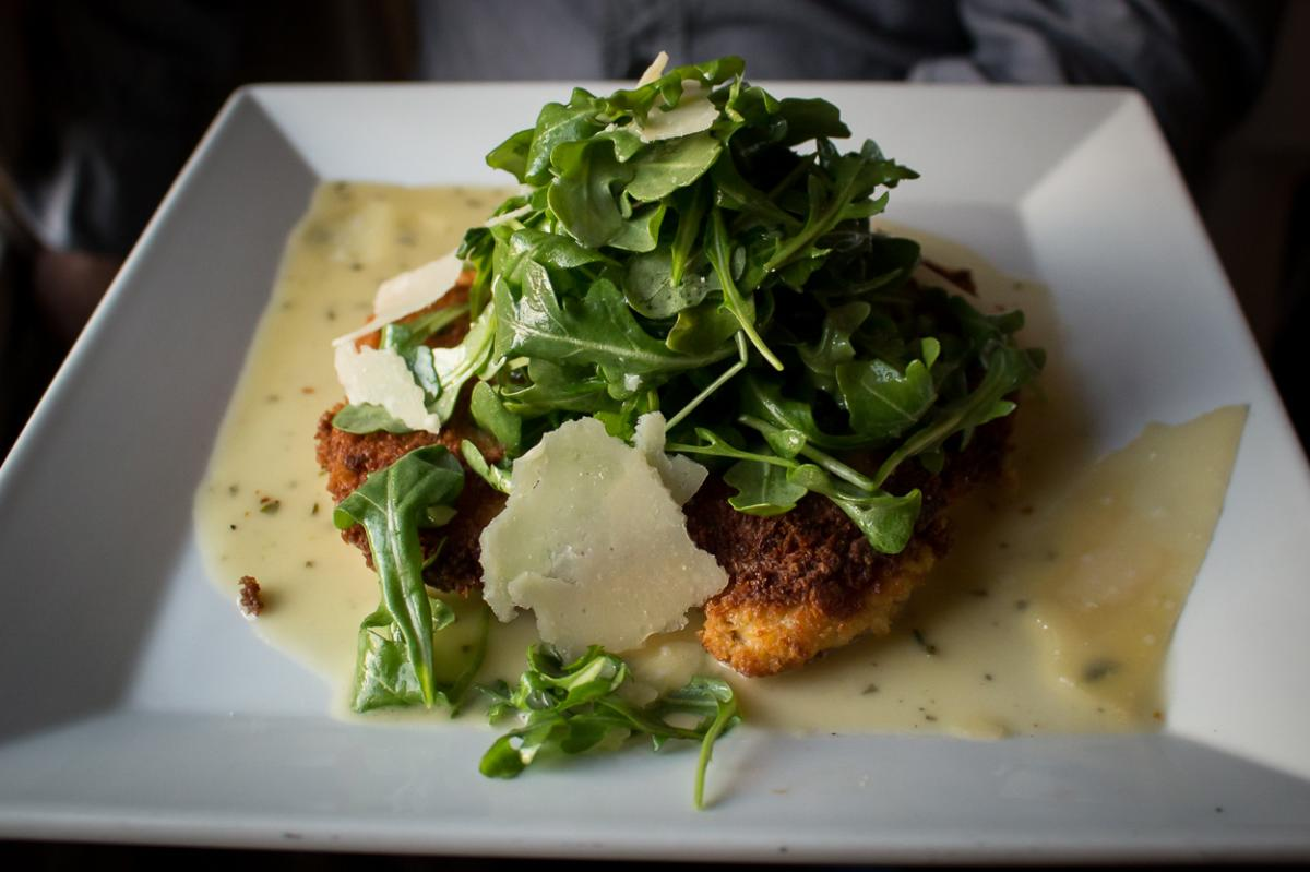Plate of Chicken Milanese topped with arugula and parmesan