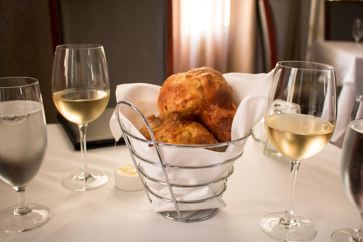 Metal basket of popovers on a table with white wine
