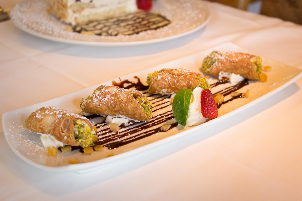 Cannoli served on rectangular plate with Italy flag colors red, white, green
