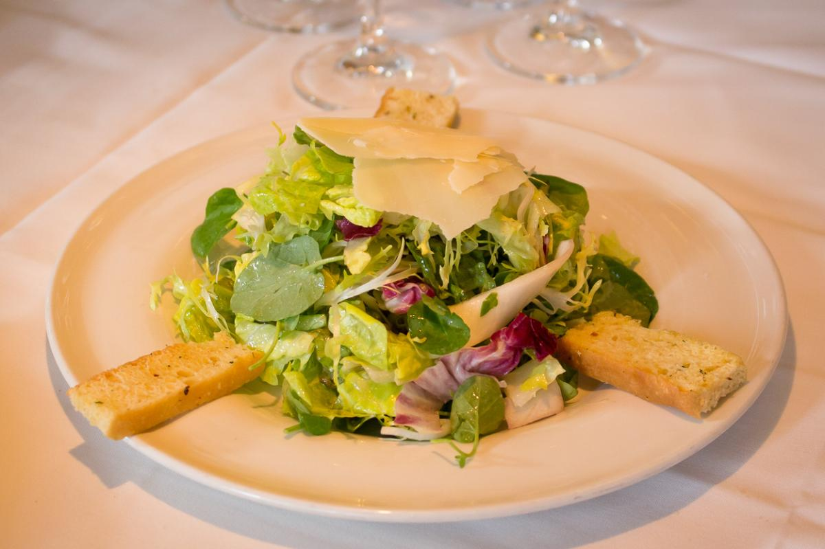 Plate of salad greens with parmesan cheese shavings and toast