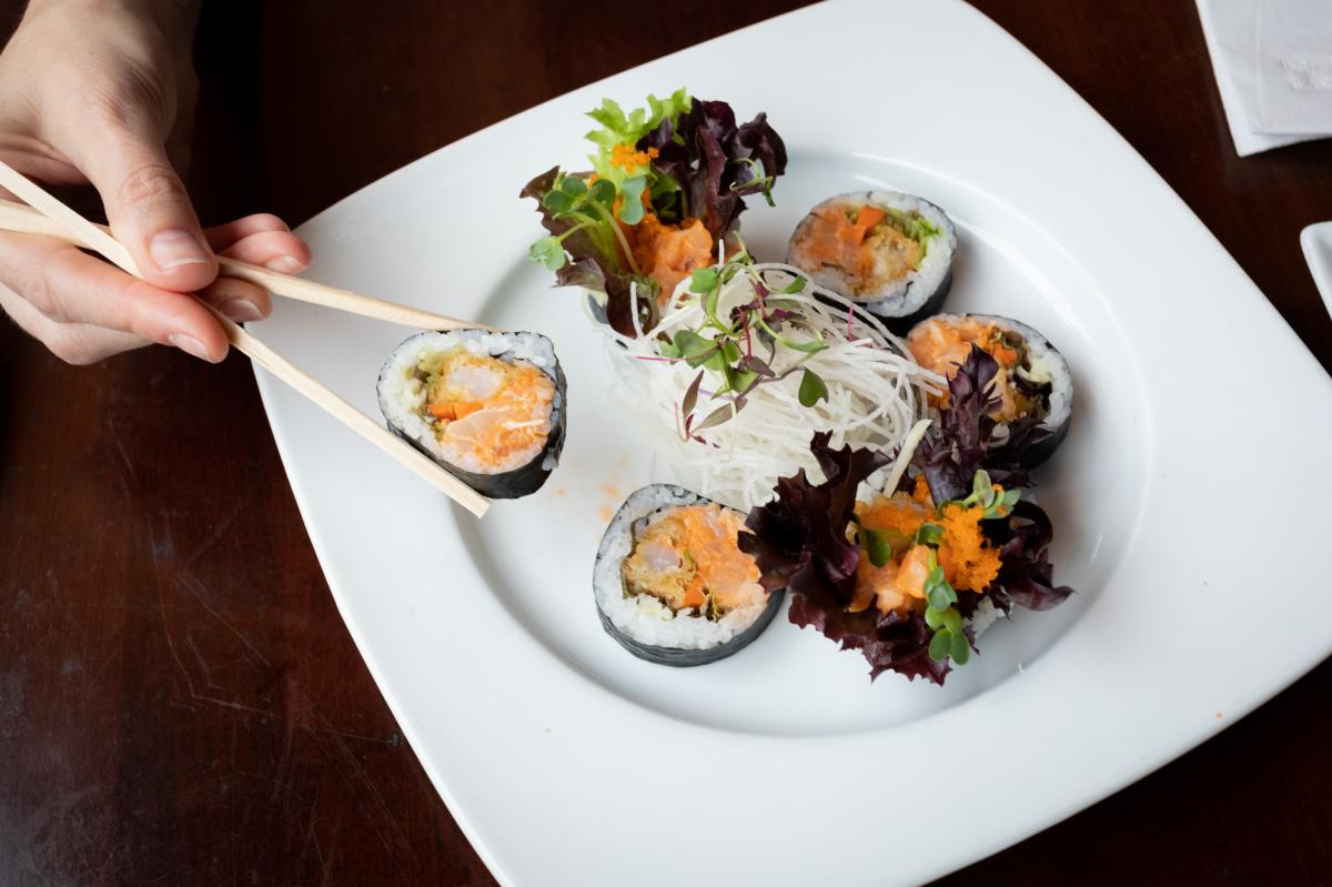 Kabuki-Aladdin-roll-hand-holding-chopsticks