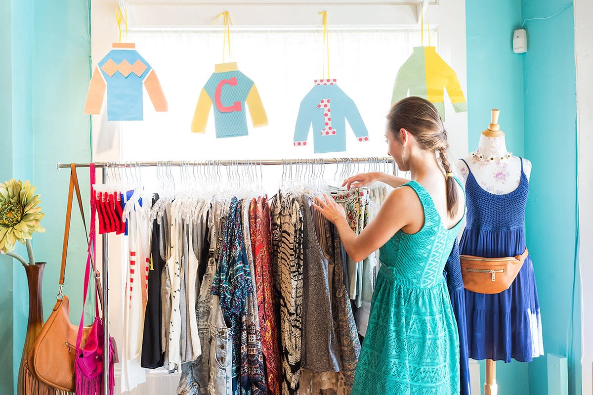 A woman in a teal dress looks through a rack of brightly colored clothing at a shop.
