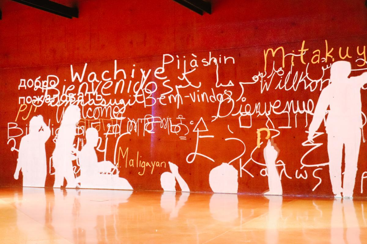 Image wall of human silhouettes signing welcome messages in various languages