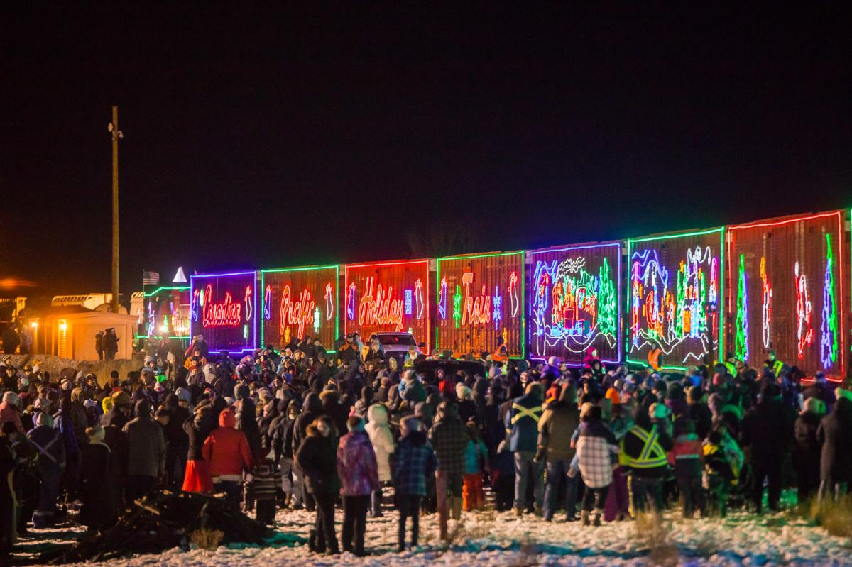 A crowd of people stand on one side of the CP Holiday Train, all the train cars are lit with Christmas lights.