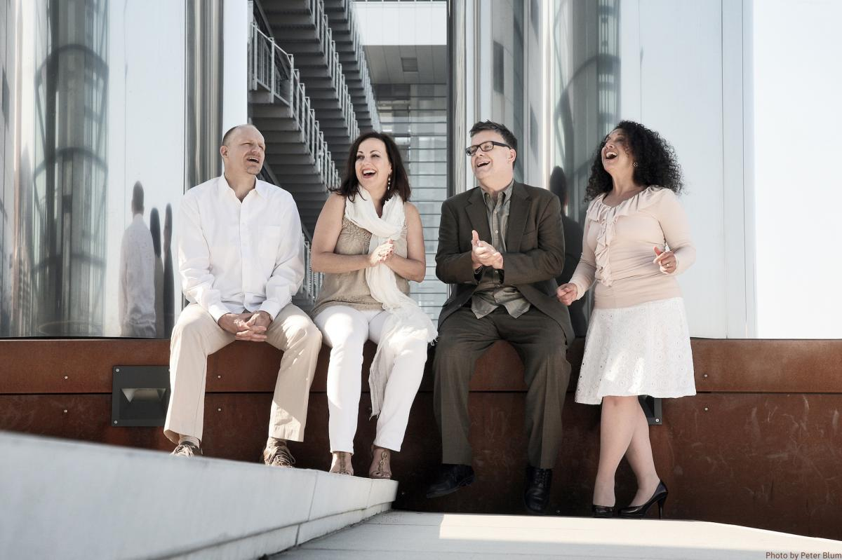 Four people sit on a bench indoors singing.