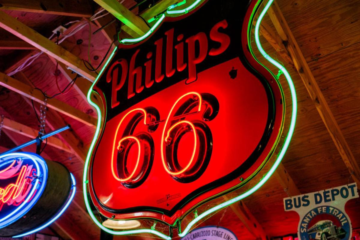 The bright neon lights illuminate a Route 66 sign.