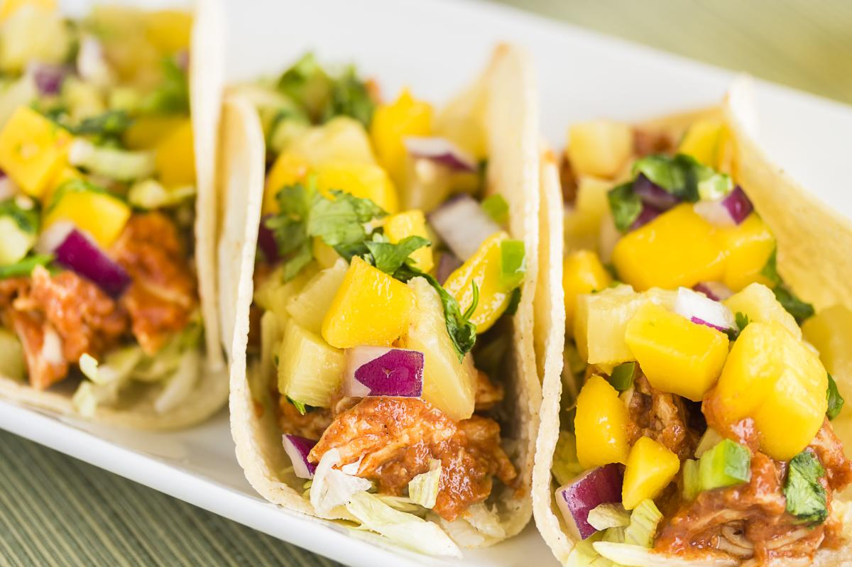 Three tacos with mango salsa.