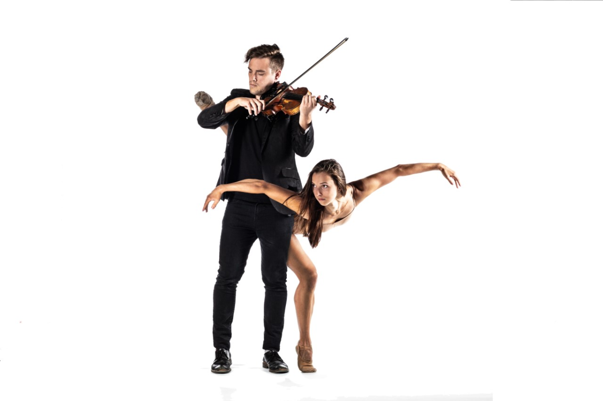 A man playing the violin while a woman dances around his back.