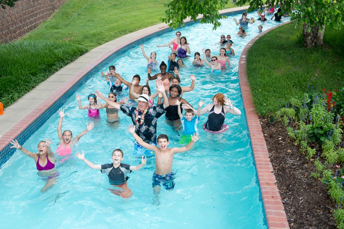 People of all ages in a lazy river with their hands up smiling