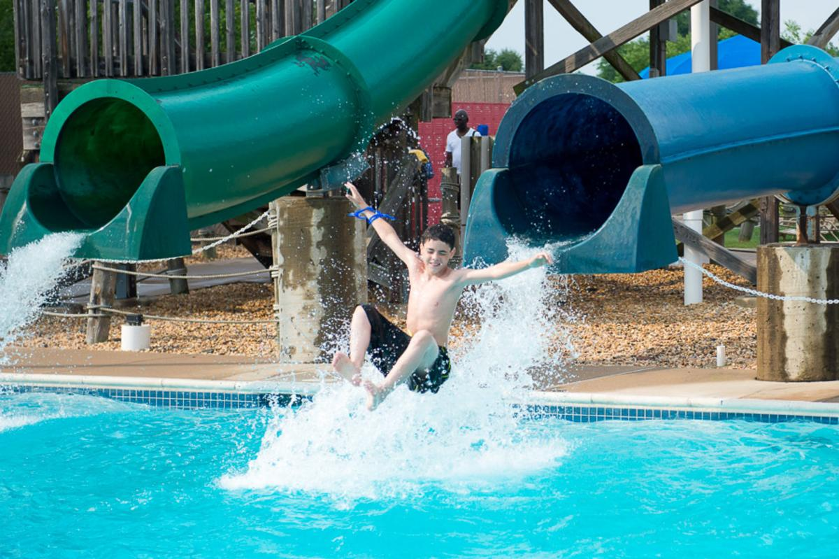 2 waterslides, 1 has a boy mid-air on his way out of the waterslide before entering the water