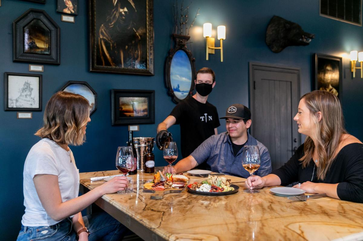 Man Pouring Wine for Group of Friends at Tooth and Nail Winery