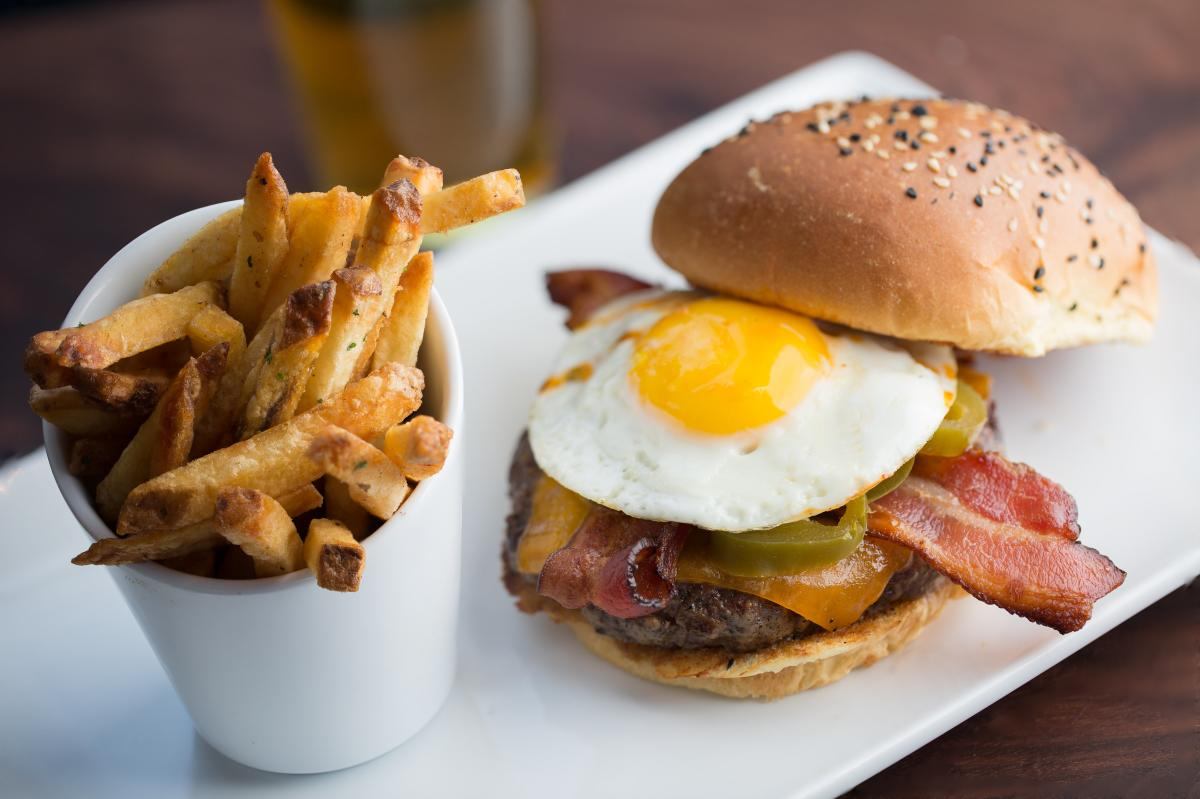Burger with fried egg and bacon and a side of fries at Eureka! in Huntington Beach