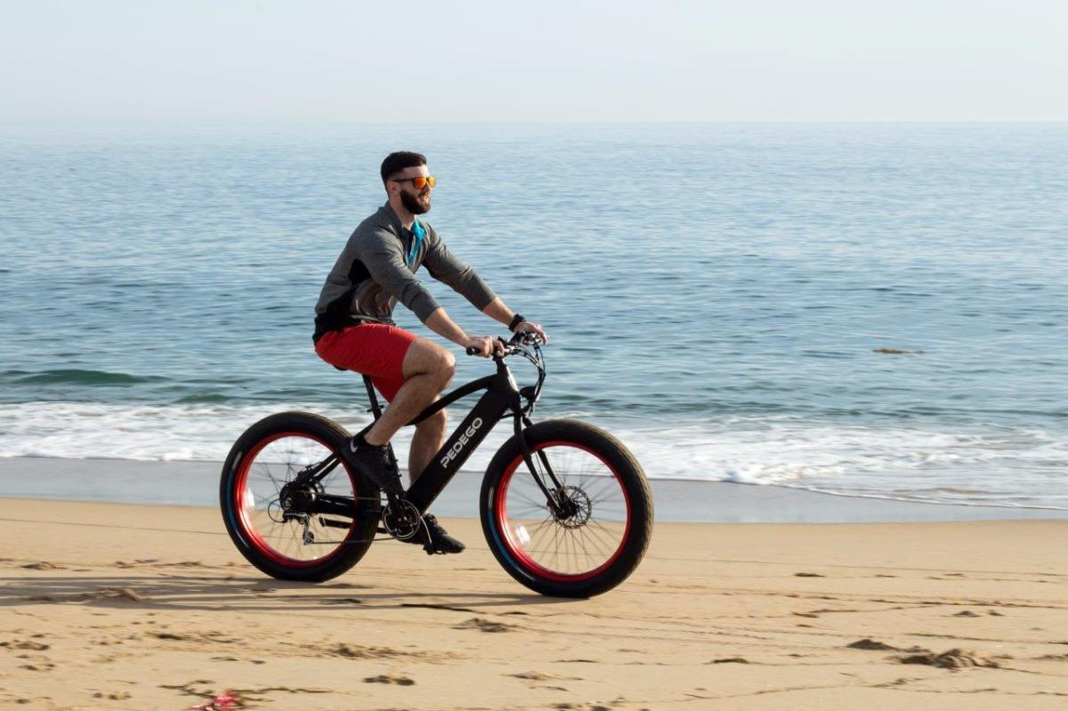 Man riding a fat-tired bike on the beach in Huntington Beach, CA