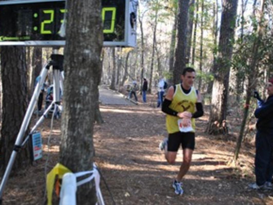Man running by the race clock in the annual Turkey Trot at Carolina Beach