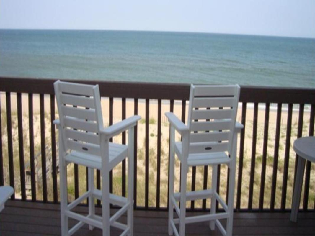 Two beach chairs facing the ocean on a wooden deck with a railing