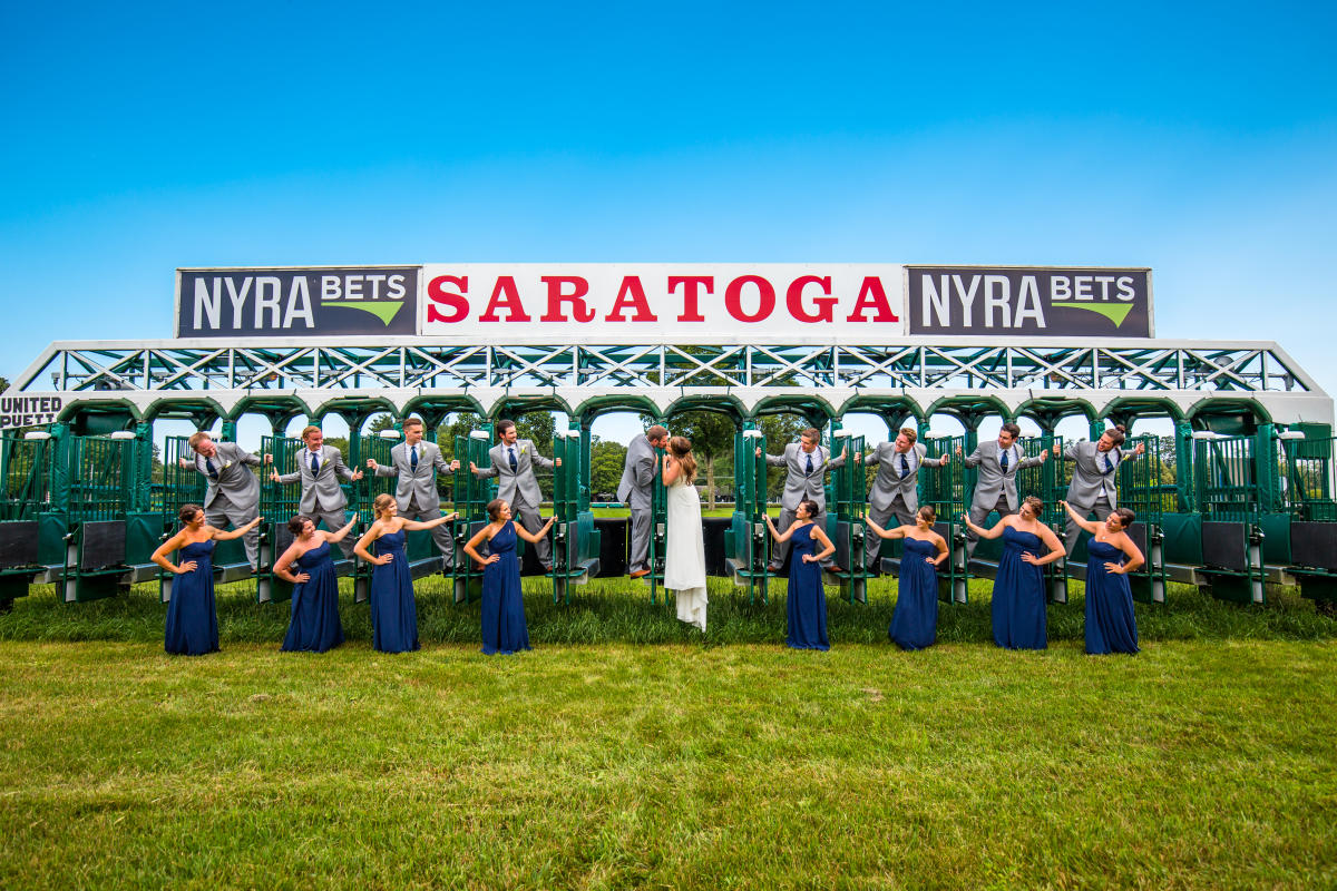 Bride, Groom, and Bridal Party posing for a picture on the Saratoga Race track's starting gates