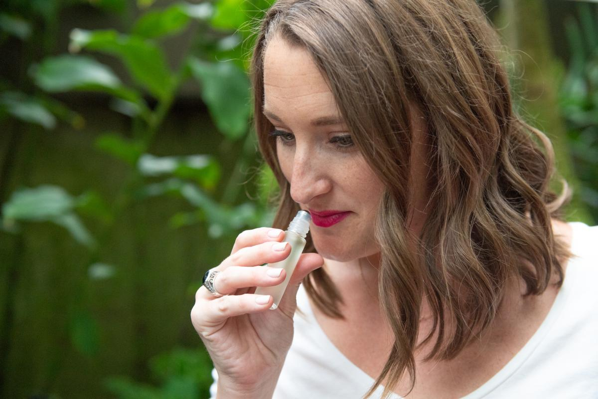 Woman sniffs scent botanical scent from vial