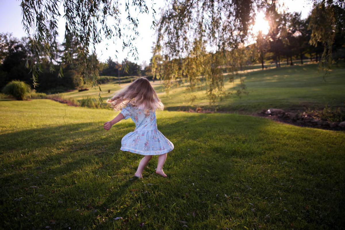 Little girl dancing outside under a tree with Movement for Joy