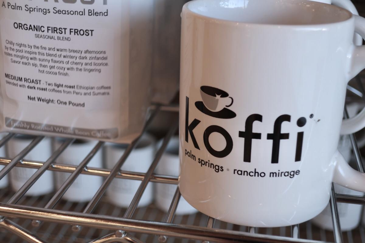 White coffee mug from Koffi shop placed on top of metal shelf.