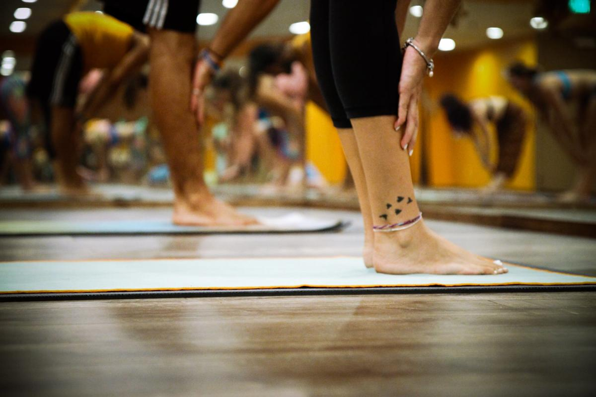 people reaching for their toes on mats in a yoga studio