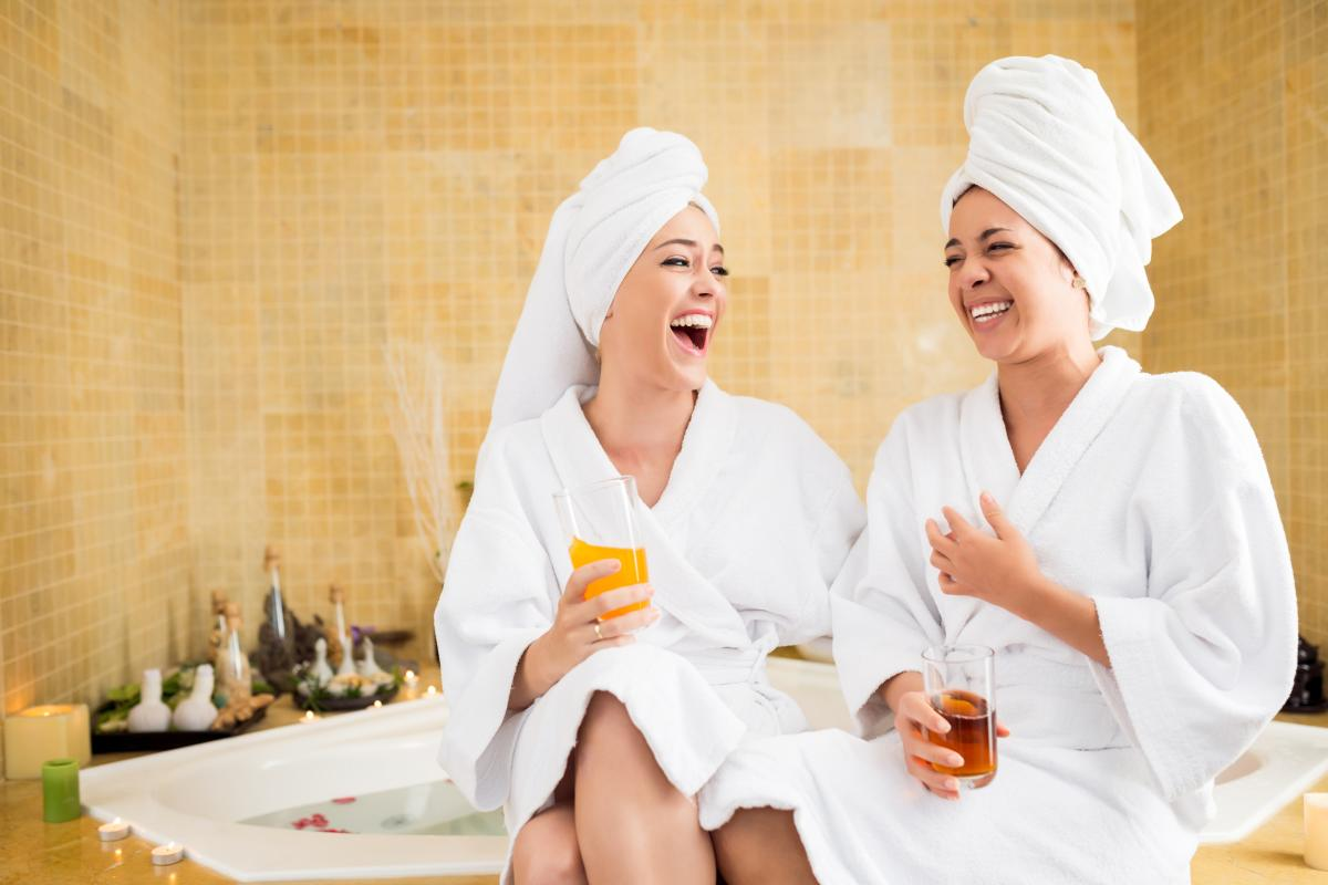 Two women in robes sitting and laughing a spa
