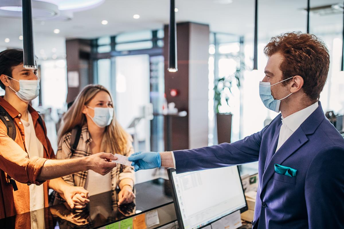 Man and women checking into hotel with face masks on