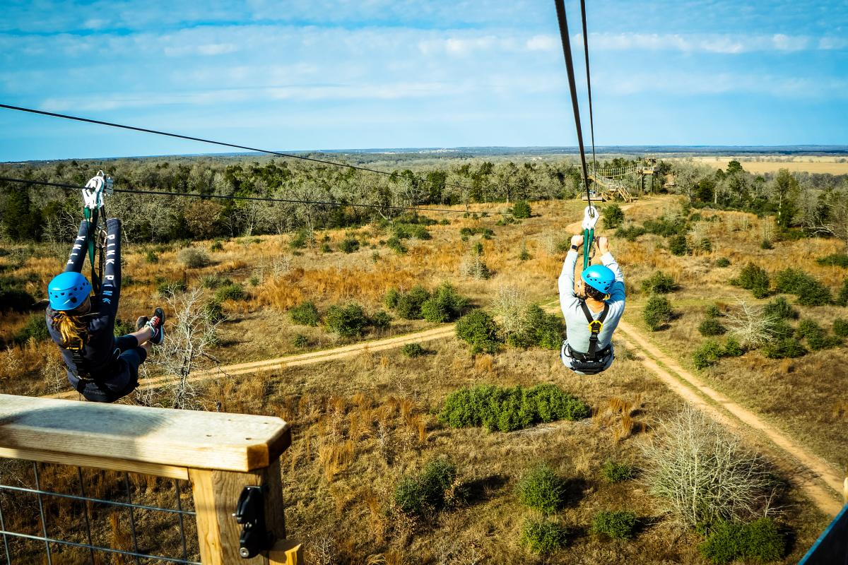 Man and woman zip lining in Lost Pines