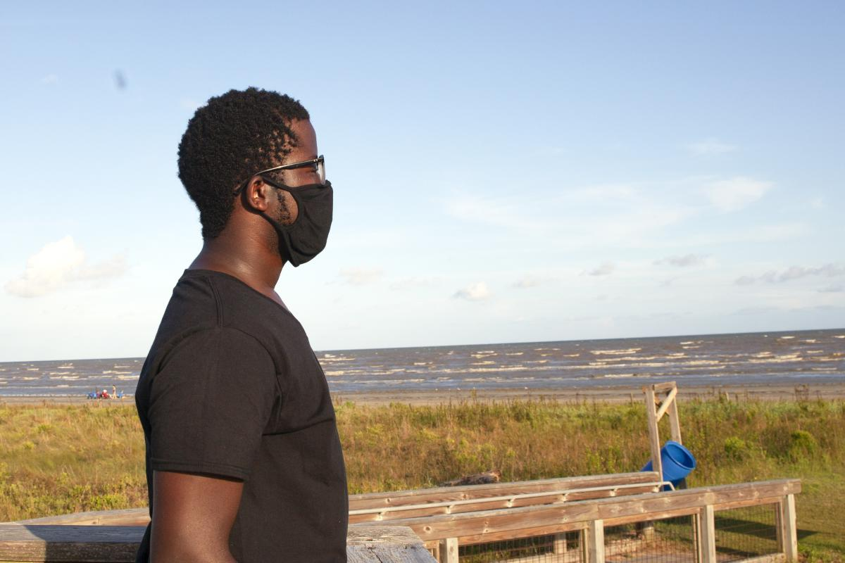 Man with face mask on overlooking Texas coastline