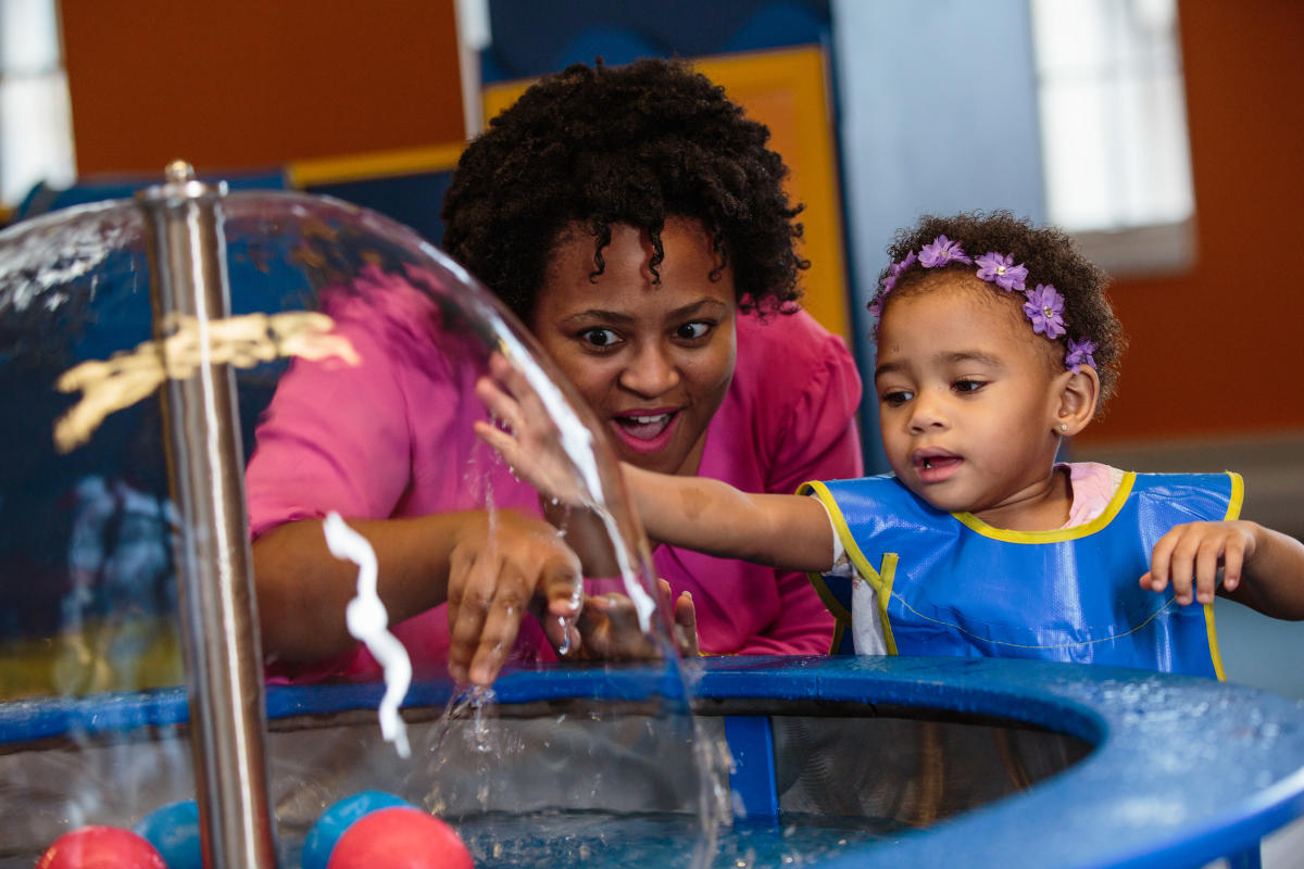 A young girl and her mother playing in a hands on water activity at COSI.